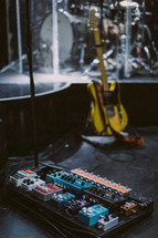 guitar pedals, guitars, and drums on stage