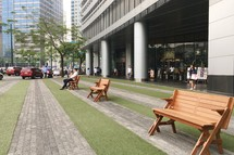 people sitting on benches along a downtown sidewalk
