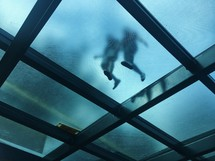 feet walking on a glass floor above