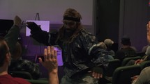 funny man giving high fives in an auditorium classroom