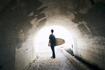 man holding a surf board walking under a tunnel