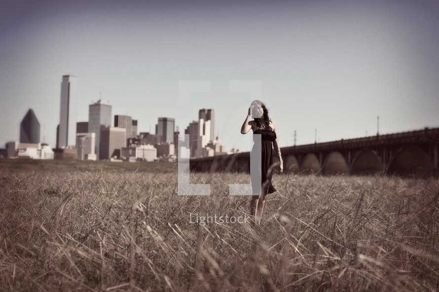 woman standing in a field in front of a city