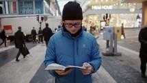 a man standing still on a city crosswalk reading a Bible