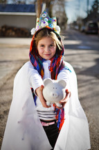 a child in a live nativity scene holding a piggy bank
