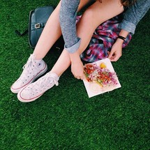 Teen girl with a taco om the grass.