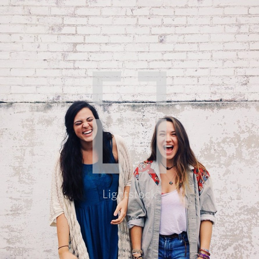 Two laughing young women against a white brick wall.