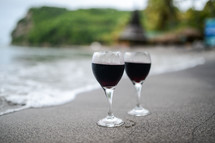 Two glasses of wine at the edge of the water on a beach.