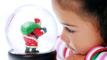 toddler girl looking at a Santa snow globe