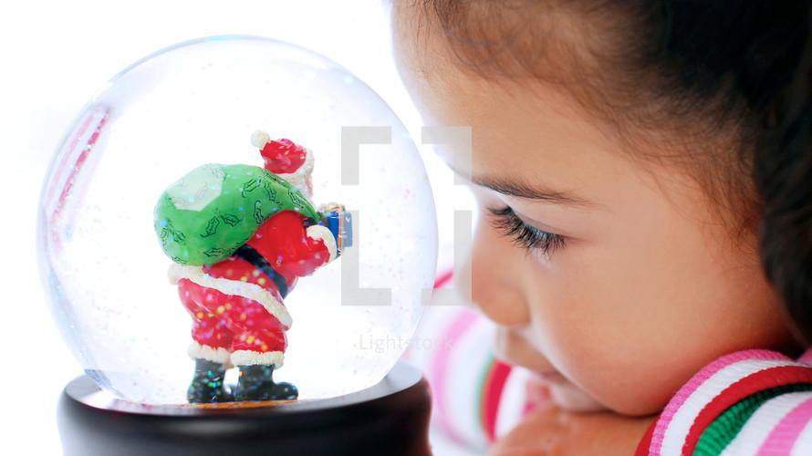 toddler girl looking at a Santa snow globe