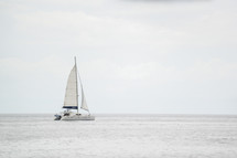 A lone sailboat on the ocean.