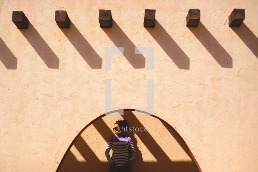 Woman standing under a stucco house.