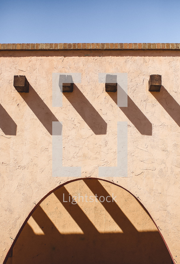 Roof and arch of a stucco house.