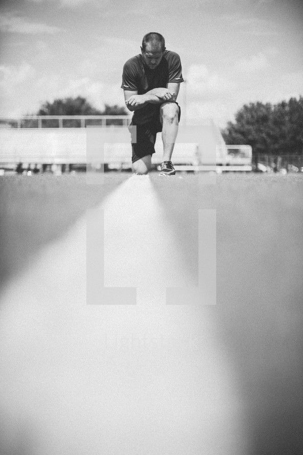 man kneeling in prayer on a football field