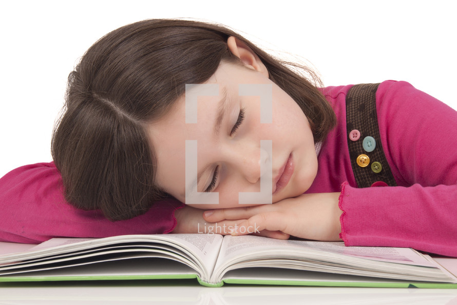 girl child resting her head on the pages of a Bible