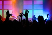 Photo during worship with hands raised in a worship service.