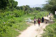 walking down a dirt road in a village