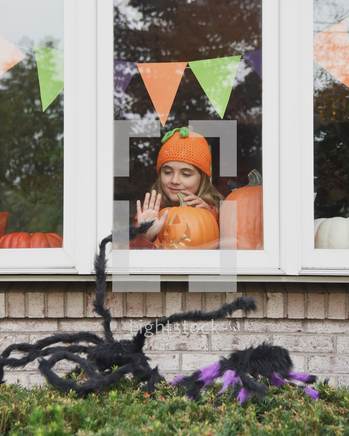 A girl with a jack-o-lantern looking out a window
