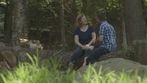 Middle aged married couple talking in the woods enjoying nature