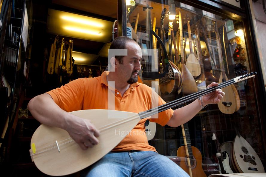 Turkish man playing Saz outside music store