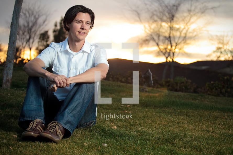 Man sitting outdoors at dusk