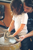 A father helping his daughter create a bowl on the potters wheel.