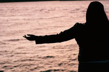 a woman with outstretched arms on a beach at sunset