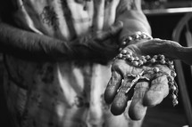elderly woman holding a rosary
