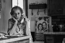 elderly woman talking on a telephone