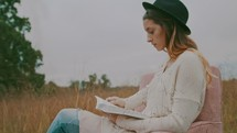 a woman sitting in a chair reading a Bible in a field