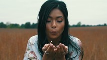 a woman blowing confetti in a field