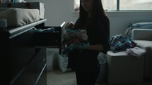 a mother folding baby clothes and putting away laundry