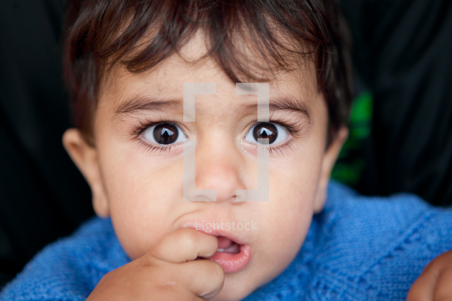 Young boy with fingers in mouth