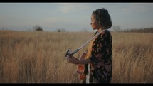 a woman standing in a field holding a guitar singing