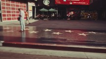 Passing through Hollywood walk of fame as people walk.