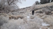 a man walking down a frozen path