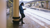 man reading a Bible leaning against a column near train tracks at a train station