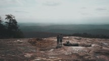 man and woman standing on a mountaintop