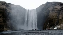 crowd of people standing in front of a waterfall