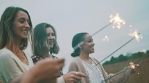 women walking through a field carrying a sparkler