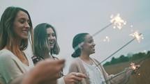 women walking through a field carrying a sparkler