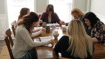 women holding hands in prayer at a women's group Bible study sitting around a table