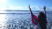 woman standing in the ocean with raised hands