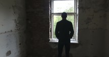 man looking out a window in an empty house
