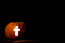 cross carved in a Jack-O-Lantern pumpkin