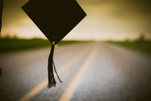 Graduate's cap and tassle hanging over the middle of the road.