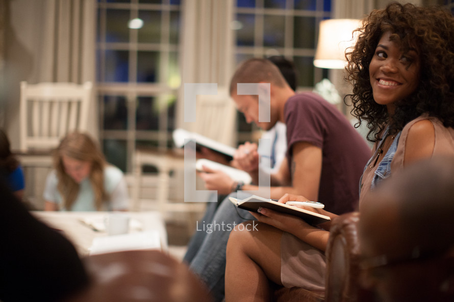 A black young adult woman smiling during a Bible study.
