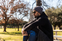 A man wearing workout clothes sits and rests in a park.
