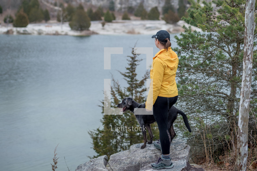 a woman and her dog looking out at a lake