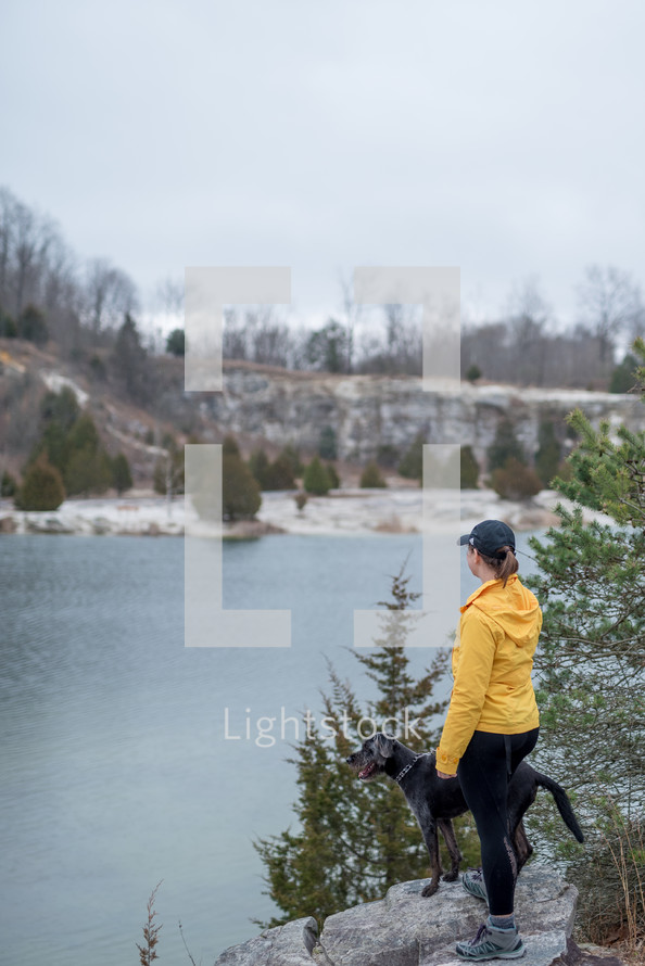 a woman with her dog standing looking out at a lake