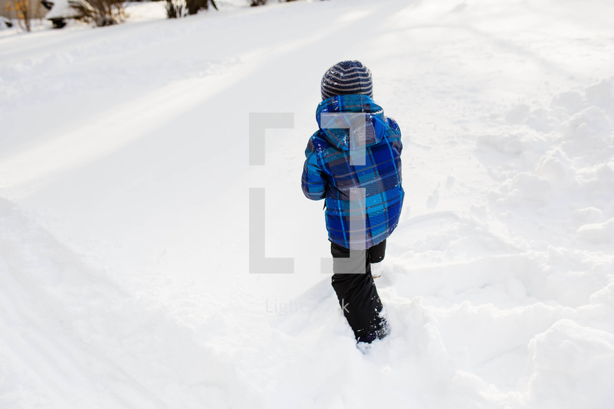 child in a snowsuit walking in snow